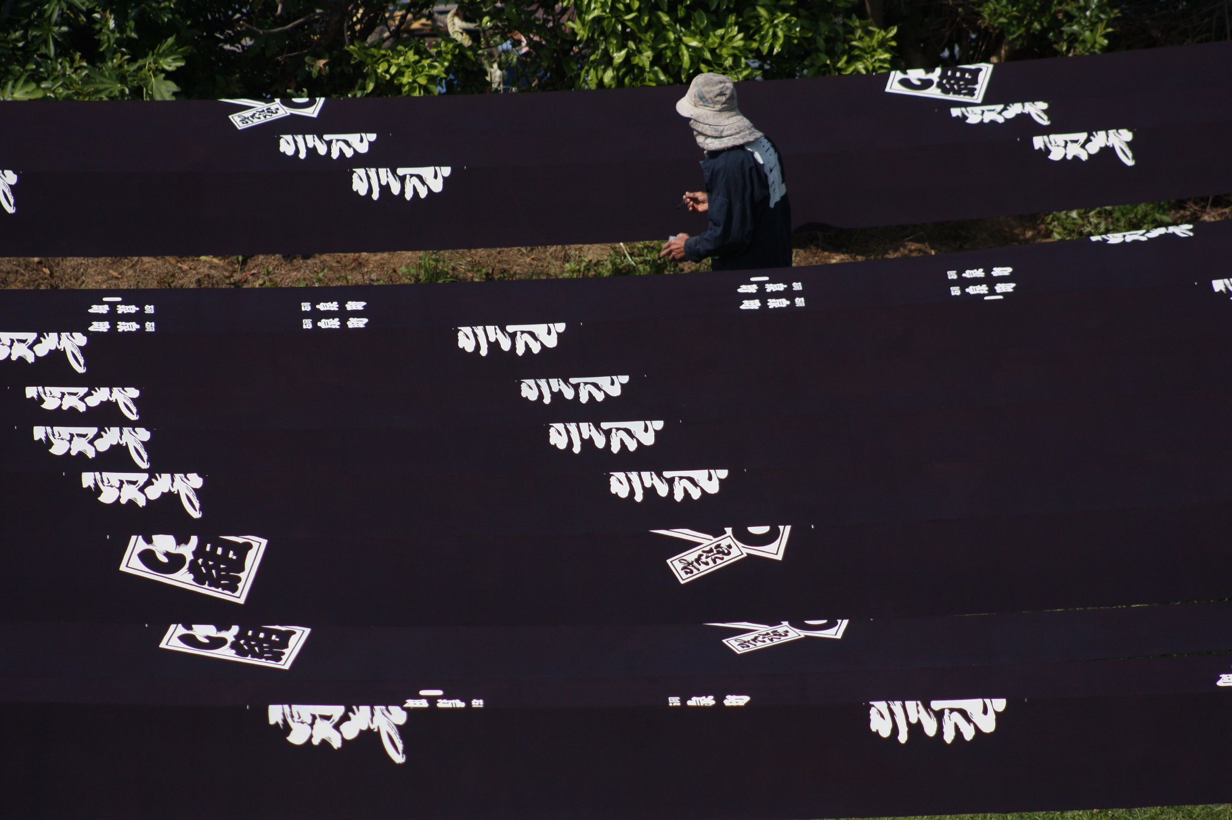 Drying the indigo dyed and katazome printed textile in open air. The patterns are traditional Japanese writing styles, such as Edo-moji and Kakuji.